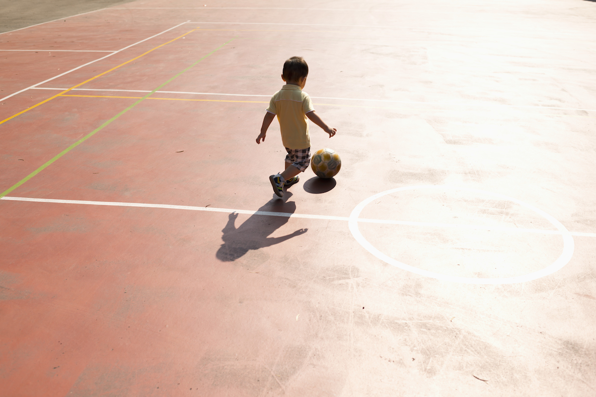Child plays a football in a complex sports ground