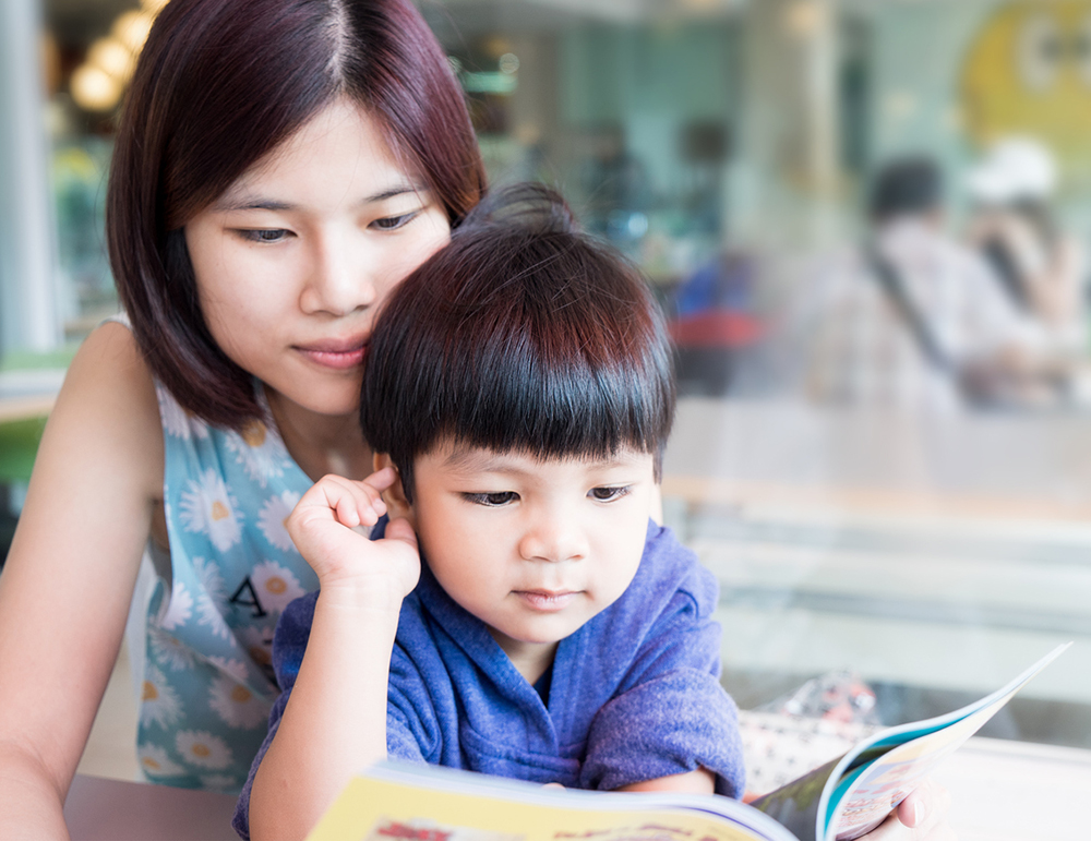 Asian Mother is teaching her son to read a book